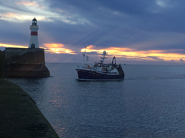 fishing boat next to lighthouse at sunset